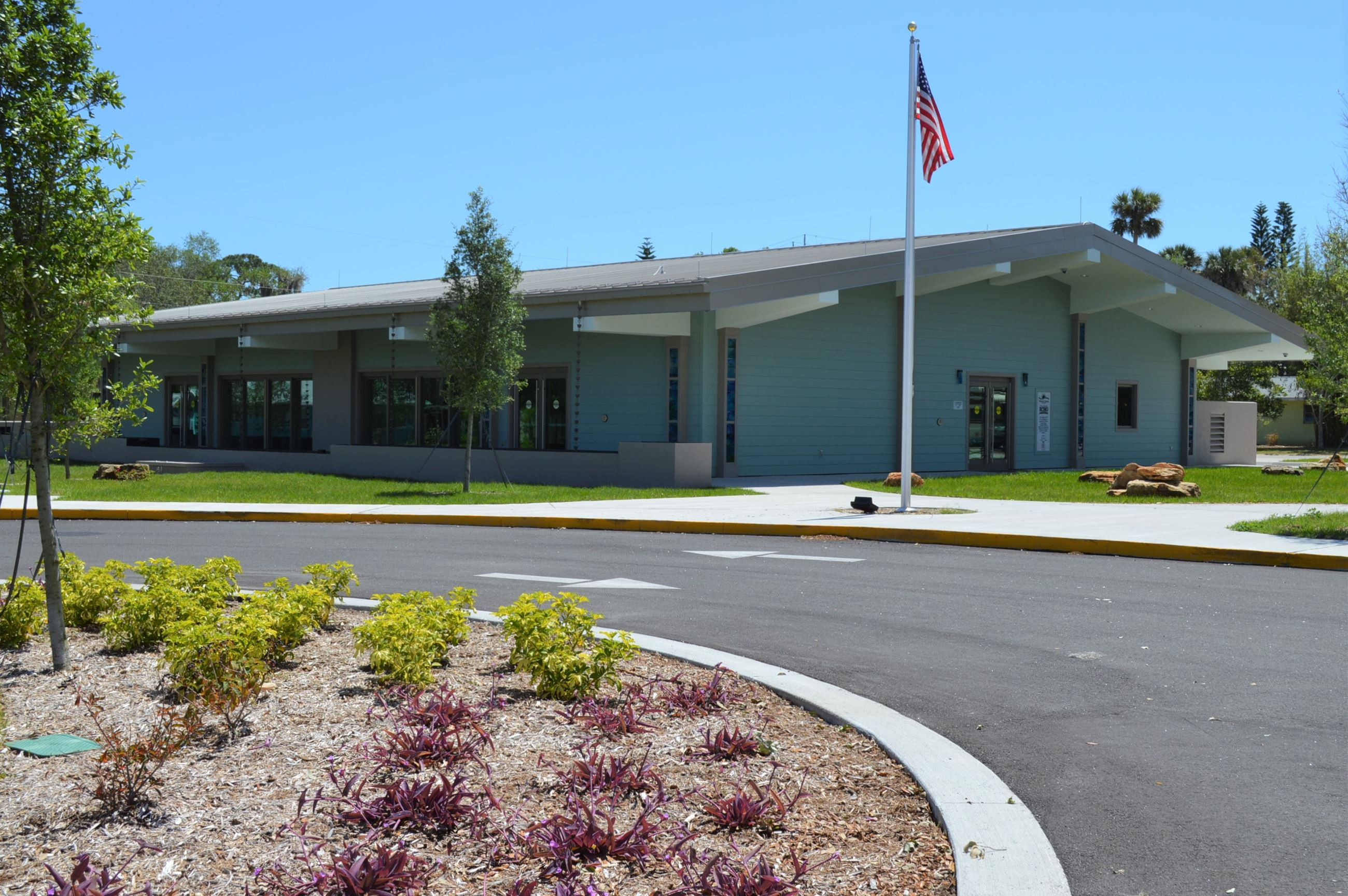 Photo of Live Oak Cultural Center exterior, single-story building with flagpole and landscaping